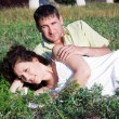 Portrait of a pretty young woman lying on grass with her boyfrie — Stock Photo