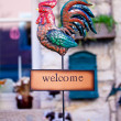 Welcome sign with iron rooster - Stock Photo