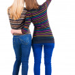 Back view of two young brunette woman pointing — Stock Photo