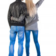 Young couple pointing at wal Back view  (woman and man). - Stock Photo