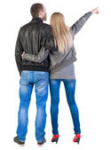 Young couple pointing at wal Back view (woman and man). — Stock Photo