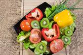 Varicoloured owoce i warzywa leżą na danie — Zdjęcie stockowe