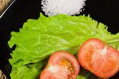 Rode rijpe tomaten met blad sla en grote zout — Stockfoto