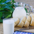 Fresh cut long loaf and milk in a jug — Stock Photo