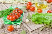 Czerwony dojrzałe pomidory z świeżej zieleni na serwetce — Zdjęcie stockowe