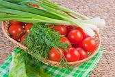Röda mogna tomater med frisk grönska på en servett — Stockfoto