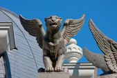 Sculptures of lions on the roof of building on a background blue — Stock Photo