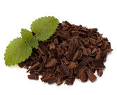 Crushed chocolate shavings pile and mint leaf — Stock Photo