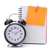 Alarm clock and blank notebook sheet. — Stock Photo