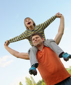 Happy son on the shoulders of the father — Stock Photo
