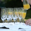 Stock Photo: Pouring orange juice into champagne flutes