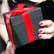 Female hand holding a gift — Stock Photo