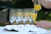 Pouring orange juice into champagne flutes — Stock Photo