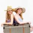Pretty sisters traveling with a shared suitcase — Stock Photo