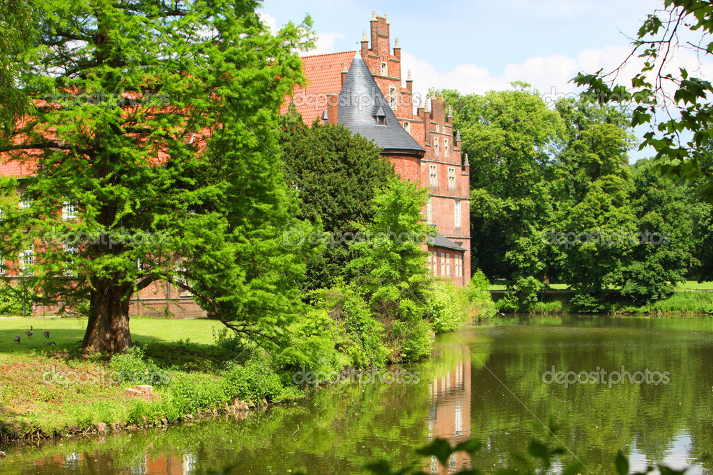 Historical red brick castle or manor in a peaceful setting overlooking a lake reflected in the calm surface — Stock Photo #11464892
