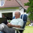 Retired man working outdoors on a laptop — Foto Stock