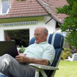 Retired man working outdoors on a laptop — Lizenzfreies Foto