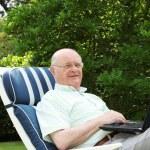 Pensioner using laptop in garden — Stock Photo