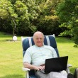 Senior musing laptop in garden — Stock Photo #11530104
