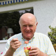 Elderly man eating fresh fruit salad — Stock Photo