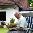 Elderly mtyping outdoors on laptop — Stock Photo #11530114