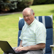 Senior man typing on a laptop — Stock Photo
