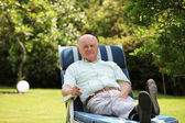 Retired man resting in the shade of a tree — Stock Photo