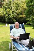 Uomo anziano usando il portatile in giardino — Foto Stock
