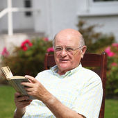 Happy pensioner relaxing with a book — Stock Photo