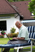 Elderly man typing outdoors on a laptop — Stock Photo