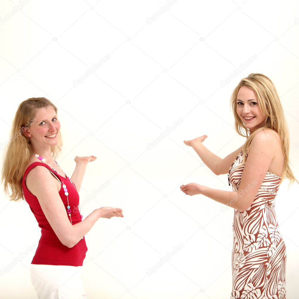 Two attractive friendly women standing facing each other with their palms out and other hands pointing to copyspace behind them as they coordinate a product placement concept — Stock Photo #11587143
