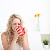 Woman drinking coffee in bed — Stock Photo