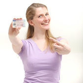 Smiling blonde woman pointing on her ID card — Stock Photo