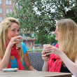 Female friends chatting over refreshments — Stock Photo
