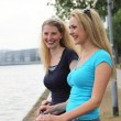 Stock Photo: Smiling friends talking alongside a river