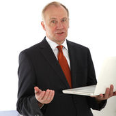 Persuasive businessman holding laptop — Stock Photo