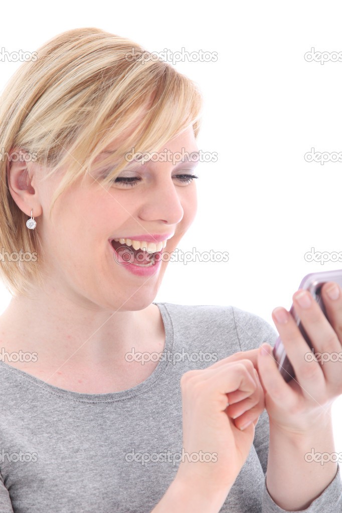 Laughing young woman reading a text message on her mobile phone isolated on white — Stock Photo #12038182