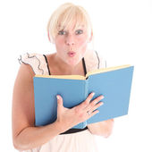Excited blonde woman reading a book — Stok fotoğraf