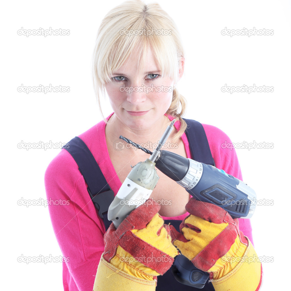 Woman DIY in dungarees and protective gloves holding a screwdriver and portable drill in front of her with a determined expression  Stock Photo #12242510