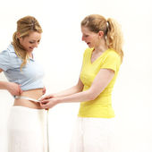 Woman measuring her friends waist — Stock Photo