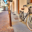 Bicycle on the street of Alba, Italy. - Stock Photo