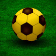 Stock Photo: A golden ball over the green grass field of soccer