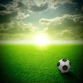 A fine green meadow with a soccer ball on it. All on sky sunset — Stock Photo