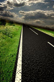 Blurred asphalt road and clouds over it — Stock Photo
