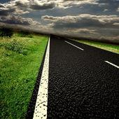 Carretera asfaltada borrosa y nubes sobre él — Foto de Stock