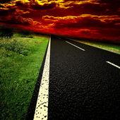 Estrada de asfalto turva e nuvens por cima — Fotografia Stock