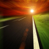 Blured Asphalt road to sun set — Stock Photo