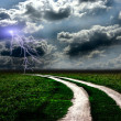 The road through meadow and the stormy sky — Stock Photo