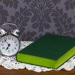 Retro alarm clock and green book - Stock Photo
