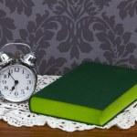 Retro alarm clock and green book — Stock Photo